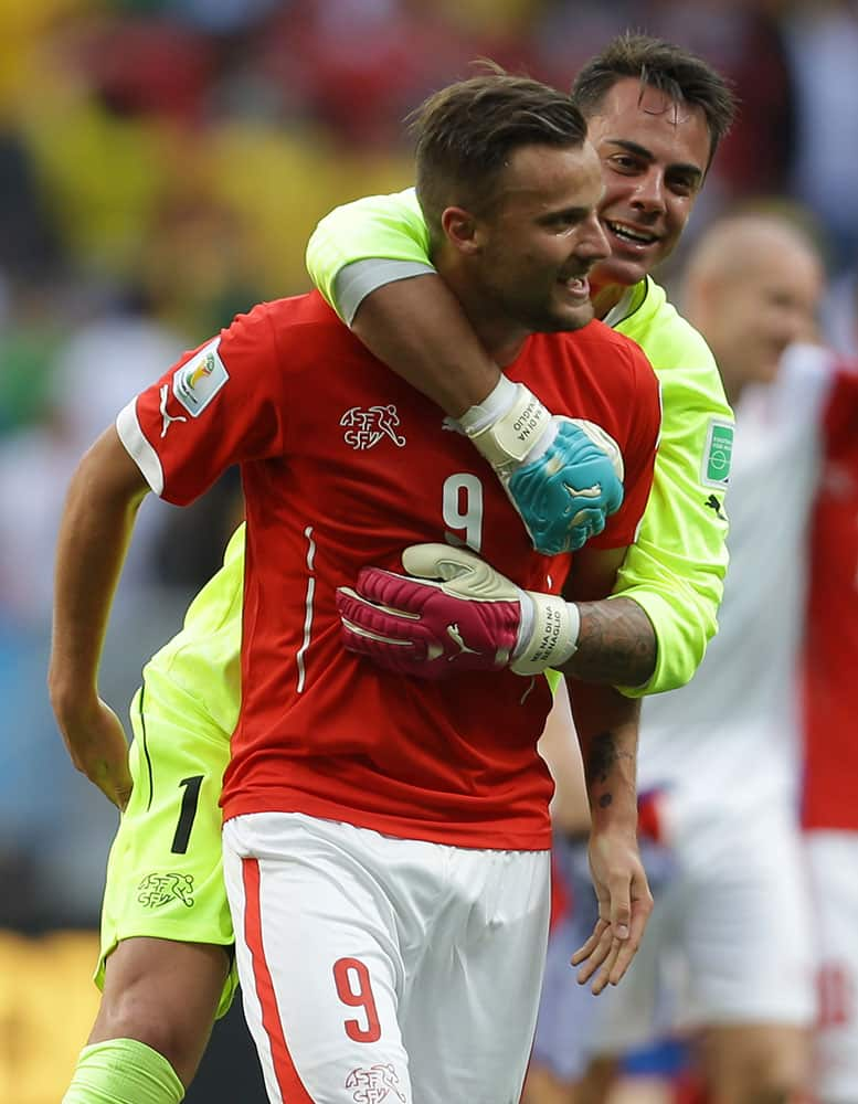 Switzerland's Haris Seferovic, front, and goalkeeper Diego Benaglio celebrate after the group E World Cup soccer match between Switzerland and Ecuador at the Estadio Nacional in Brasilia, Brazil.