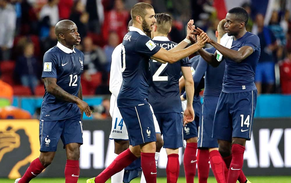 France's Karim Benzema, center, is congratulated by France's Blaise Matuidi (14), Rio Mavubaand (12) and other teammates after their 3-0 victory over Honduras during the group E World Cup soccer match between France and Honduras at the Estadio Beira-Rio in Porto Alegre, Brazil.