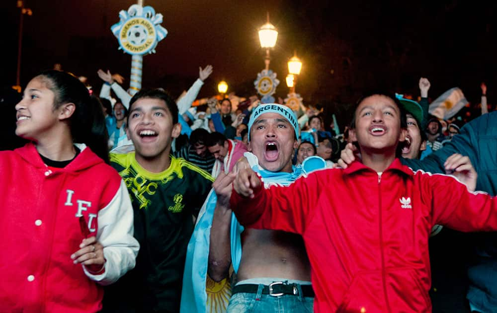 Argentina soccer fans celebrate their team's goal against Bosnia while watching the World Cup soccer game on an outdoor display set up in Buenos Aires, Argentina.