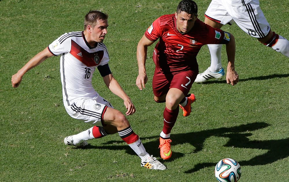Portugal's Cristiano Ronaldo and Germany's Philipp Lahm go for the ball during the group G World Cup soccer match between Germany and Portugal at the Arena Fonte Nova in Salvador, Brazil.