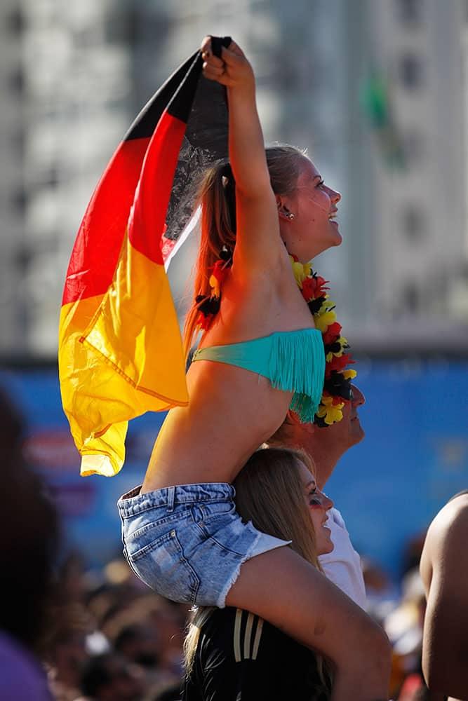 Soccer fans celebrate the last goal scored by Germany during a live broadcast of the World Cup match between Portugal and Germany, inside the FIFA Fan Fest area on Copacabana beach, in Rio de Janeiro, Brazil.