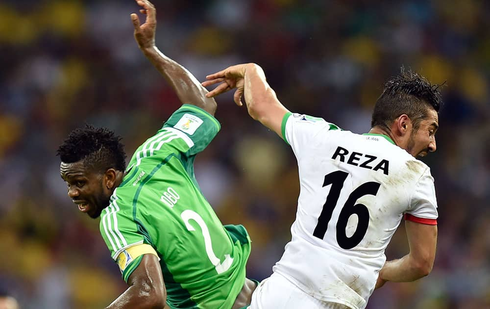 Nigeria's Joseph Yobo, left, challenges Iran's Reza Ghoochannejhad during the group F World Cup soccer match between Iran and Nigeria at the Arena da Baixada in Curitiba, Brazil.