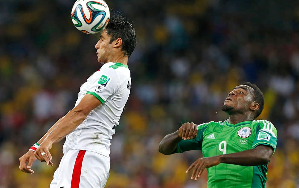 Iran's Amirhossein Sadeghi heads the ball in front of Nigeria's Emmanuel Emenike during the group F World Cup soccer match between Iran and Nigeria at the Arena da Baixada in Curitiba, Brazil.