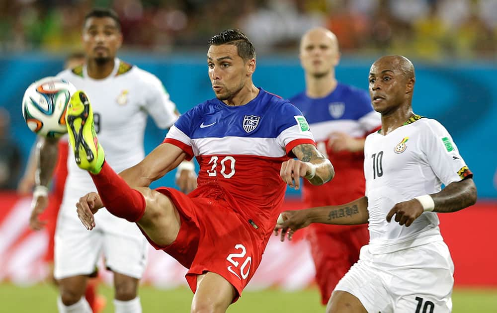 United States' Geoff Cameron, left, kicks the ball clear from Ghana's Andre Ayew during the group G World Cup soccer match between Ghana and the United States at the Arena das Dunas in Natal, Brazil.