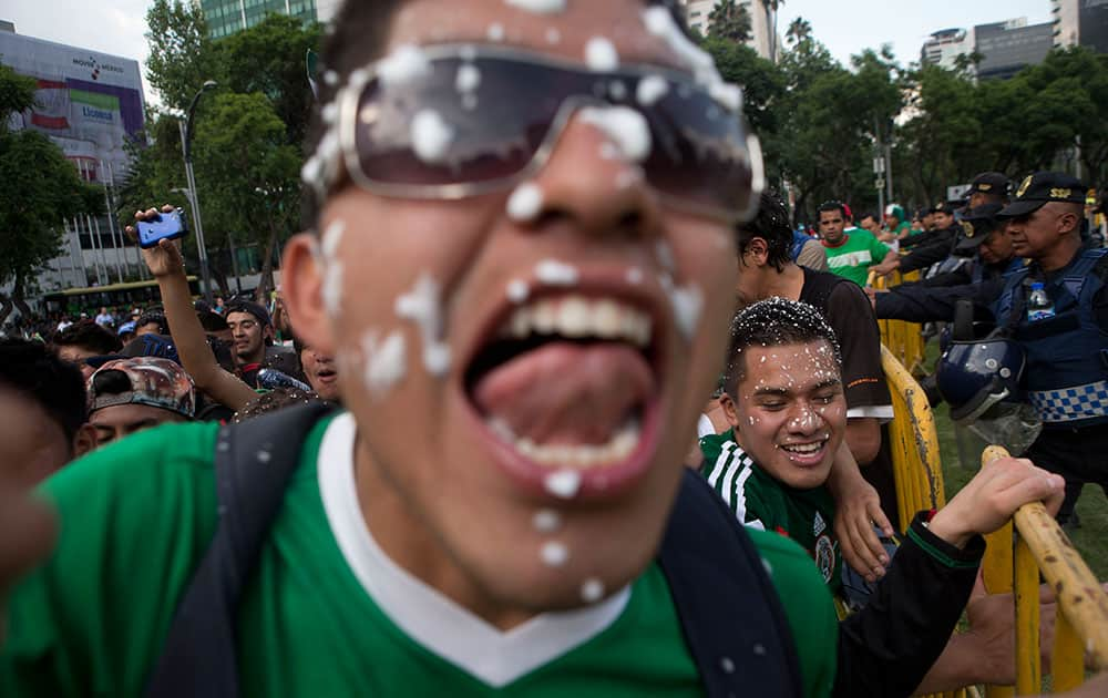 Mexico soccer fans celebrate at the Independence Monument after their team tied with Brazil in their 2014 World Cup soccer match, in Mexico City.