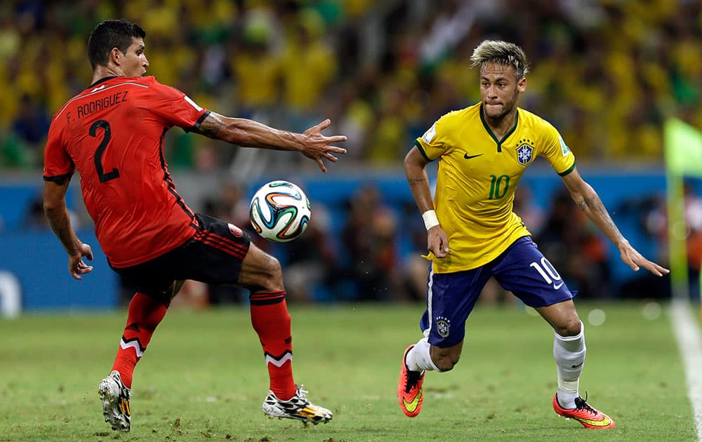 Brazil's Neymar, right, gets past Mexico's Francisco Rodriguez during the group A World Cup soccer match between Brazil and Mexico at the Arena Castelao in Fortaleza, Brazil.