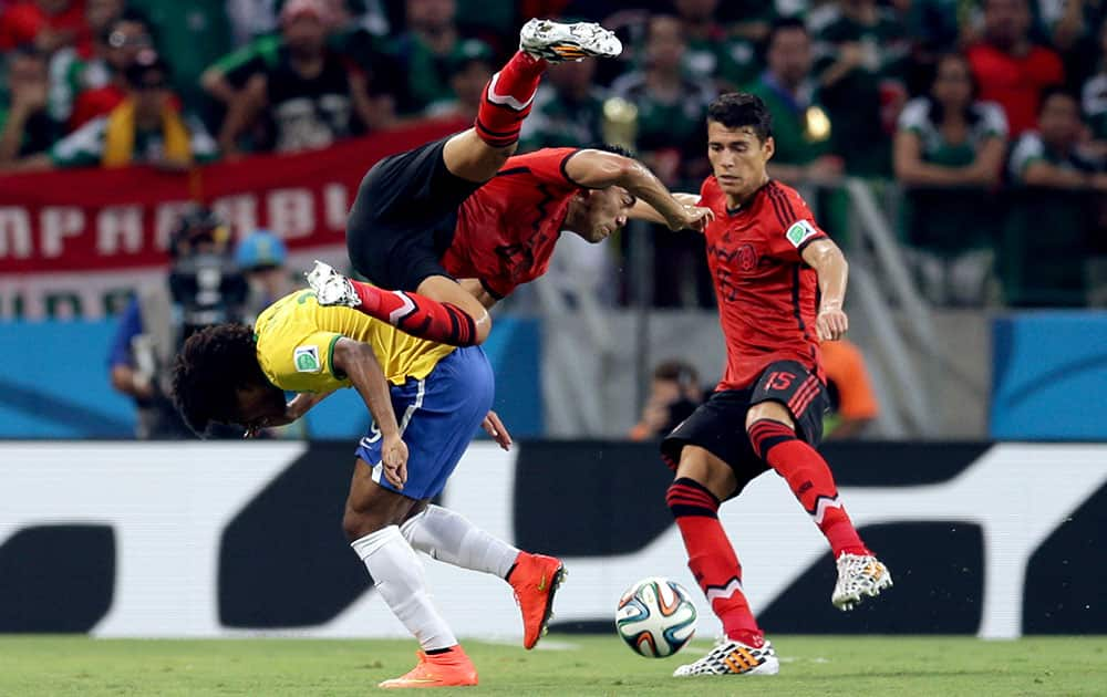 Brazil's Willian, left, challenges Mexico's Marco Fabian, center, and Hector Moreno during the group A World Cup soccer match between Brazil and Mexico at the Arena Castelao in Fortaleza, Brazil.