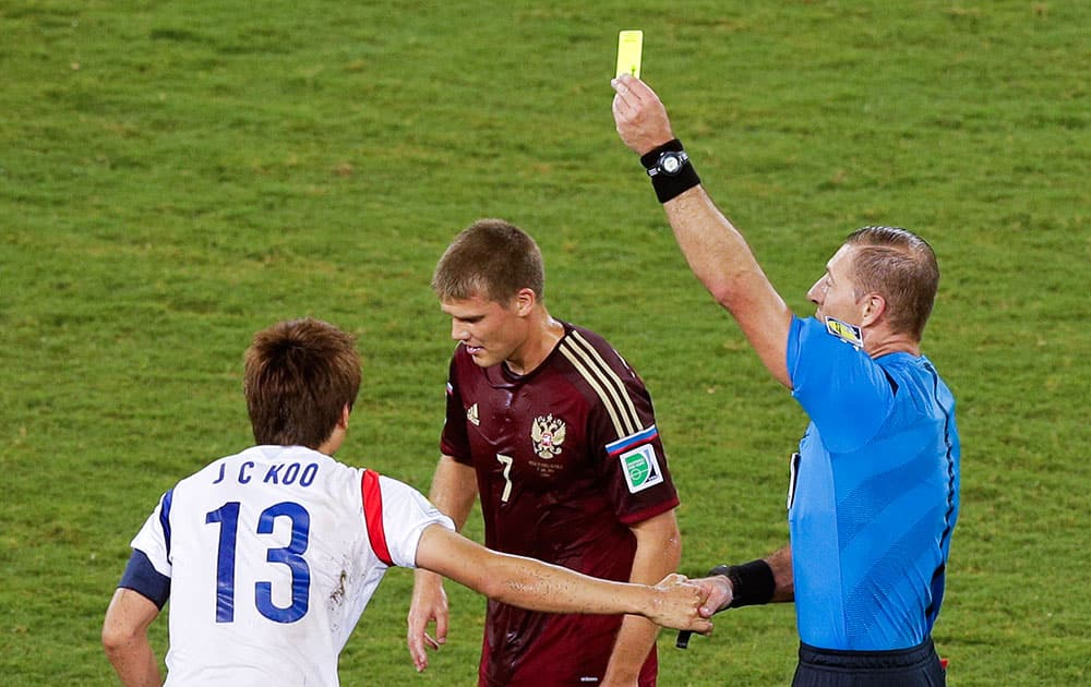 Referee Nestor Pitana, from Argentina, right, books South Korea's Koo Ja-cheol (13) during the group H World Cup soccer match between Russia and South Korea at the Arena Pantanal in Cuiaba, Brazil.