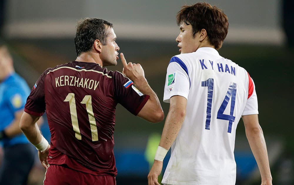 Russia's Alexander Kerzhakov, left, gives a quiet sign to South Korea's Han Kook-young during the group H World Cup soccer match between Russia and South Korea at the Arena Pantanal in Cuiaba, Brazil.