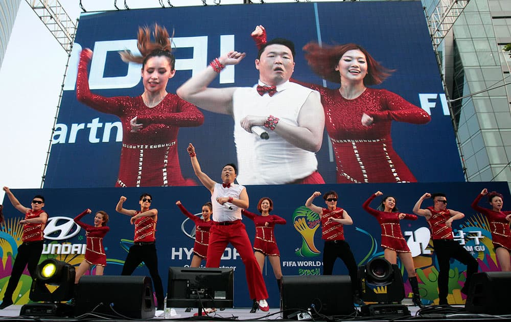 South Korean rapper PSY,center, performs before a TV broadcasting of the group H World Cup soccer match between Russia and South Korea, at a public viewing venue in Seoul, South Korea.