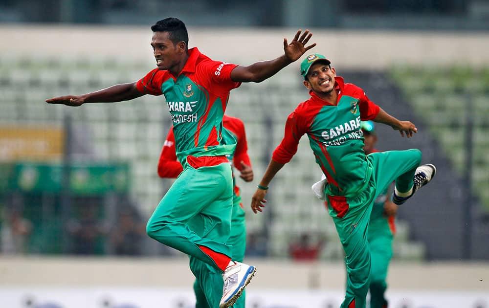Bangladesh's Al-Amin Hossain, left, celebrates with teammate Nasir Hossain the dismissal of India's Akshar Patel during their second one-day International cricket match in Dhaka, Bangladesh.