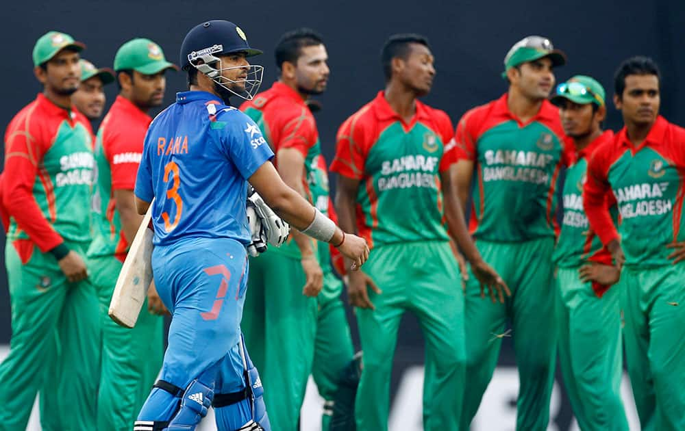 India's captain Suresh Raina, foreground, walks back to the pavilion after his dismissal during their second one-day International cricket match against Bangladesh in Dhaka, Bangladesh.