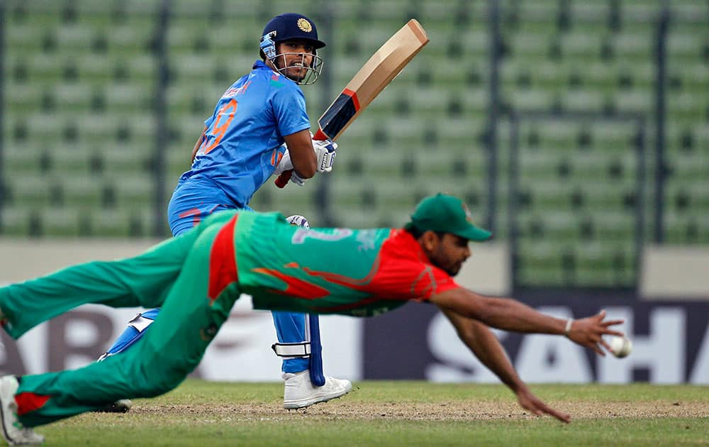 India's Umesh Yadav plays a shot as Bangladesh's Mashrafe Mortaza dives to stop the ball during their second one-day International cricket match against Bangladesh in Dhaka, Bangladesh.