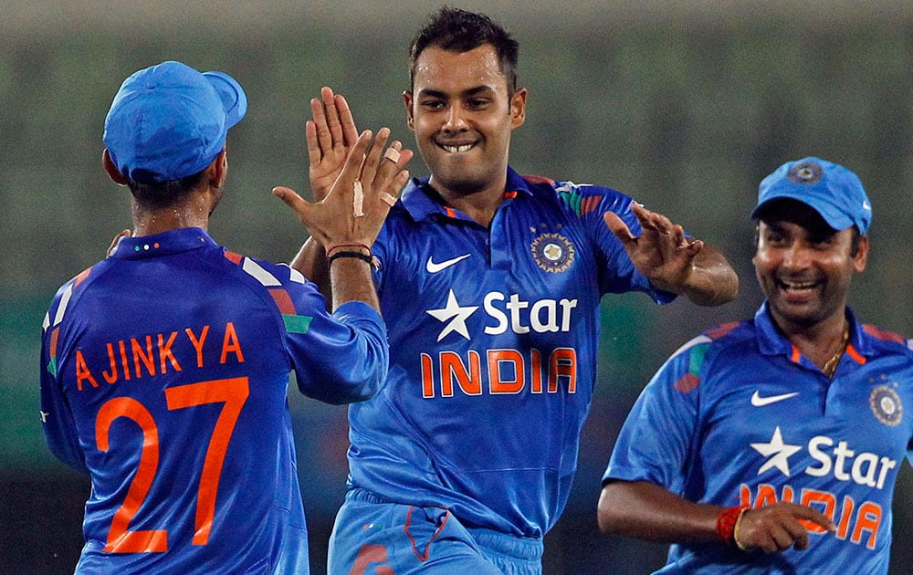 India's Stuart Binny, center, celebrates with teammates after the wicket of Bangladesh's Mahmudullah during their second one-day International cricket match in Dhaka, Bangladesh.