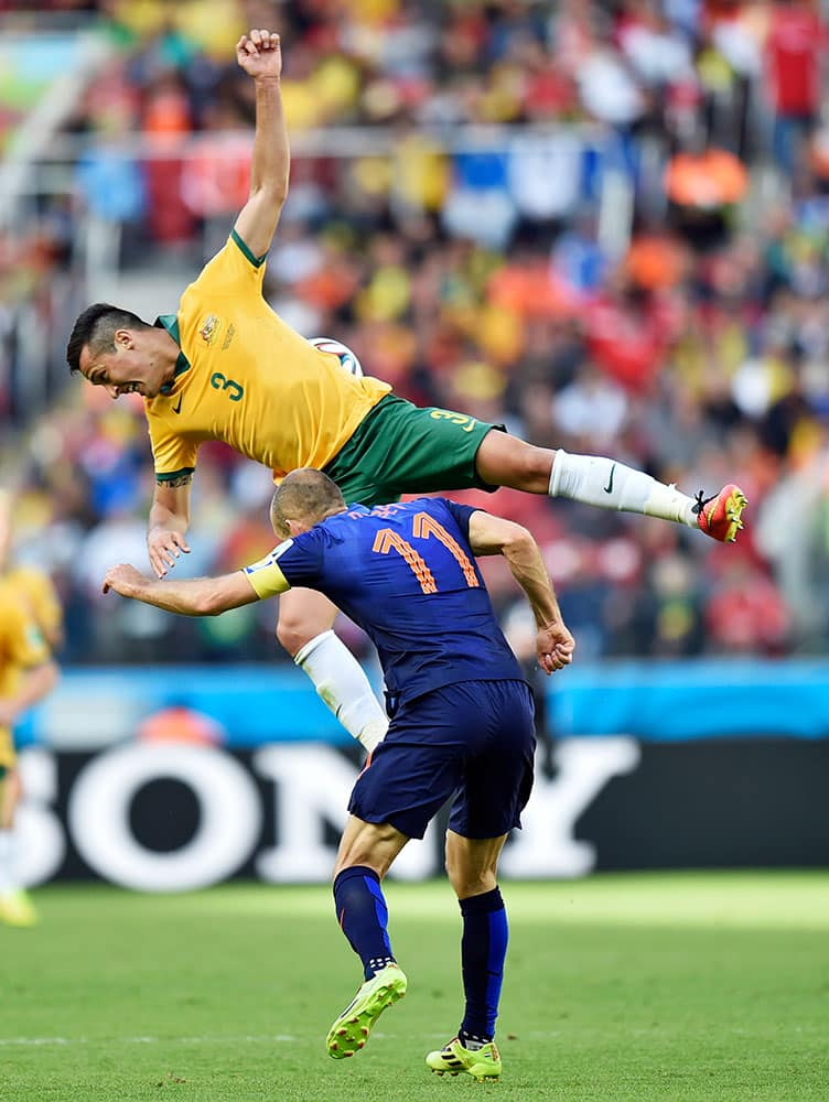 Australia's Jason Davidson, top, rises above Australia's Tommy Oar during the group B World Cup soccer match between Australia and the Netherlands at the Estadio Beira-Rio in Porto Alegre, Brazil.