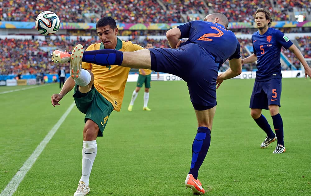 Australia's Tim Cahill, left, and Netherlands' Ron Vlaar battle for the ball during the group B World Cup soccer match between Australia and the Netherlands at the Estadio Beira-Rio in Porto Alegre, Brazil.