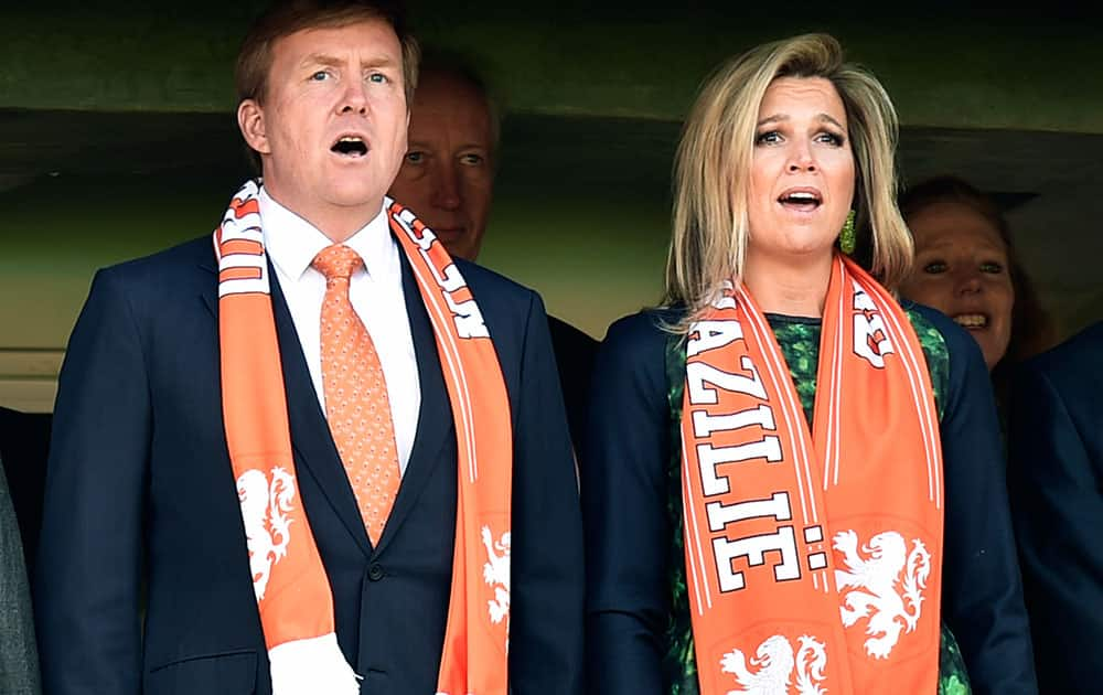 Dutch King Willem-Alexanderd and his wife Queen Maxima sing the national anthem before the start of the group B World Cup soccer match between Australia and the Netherlands at the Estadio Beira-Rio in Porto Alegre, Brazil.