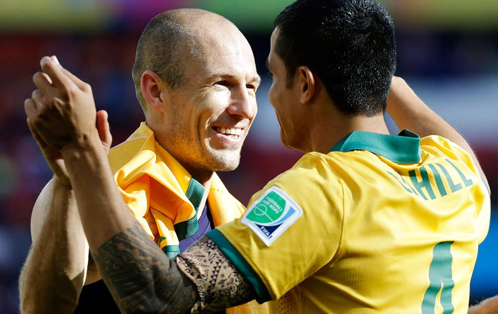 Netherlands' Arjen Robben, left, hugs Australia's Tim Cahill following the team's 3-2 loss to the Netherlands during the group B World Cup soccer match between Australia and the Netherlands at the Estadio Beira-Rio in Porto Alegre, Brazil.
