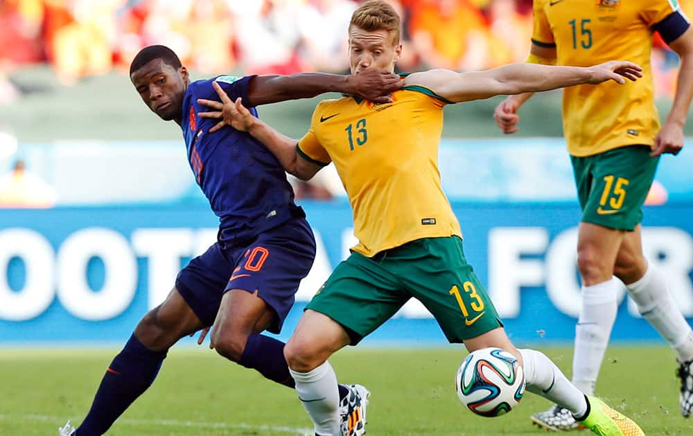 Netherlands' Georginio Wijnaldum, left, grapples with Australia's Oliver Bozanic during the group B World Cup soccer match between Australia and the Netherlands at the Estadio Beira-Rio in Porto Alegre, Brazil.