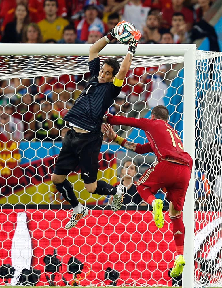 Chile's goalkeeper Claudio Bravo makes a save against Spain's Sergio Ramos during the group B World Cup soccer match between Spain and Chile at the Maracana Stadium in Rio de Janeiro, Brazil.