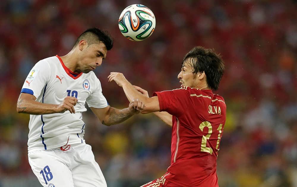 Chile's Gonzalo Jara, left, and Spain's David Silva battle for the ball during the group B World Cup soccer match between Spain and Chile at the Maracana Stadium in Rio de Janeiro, Brazil.