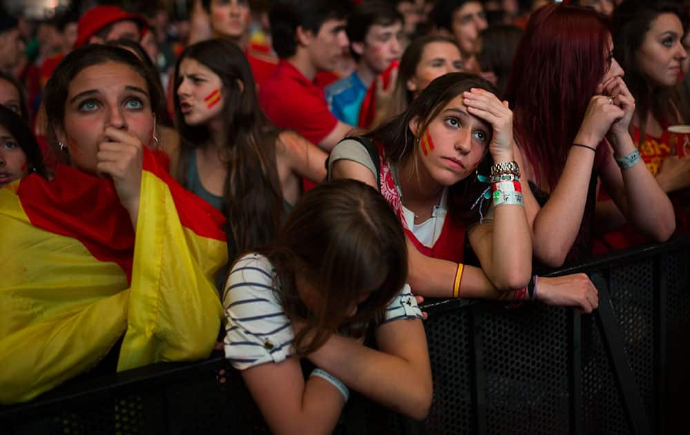 Spanish soccer fans gesture as they watch on a giant display the World Cup soccer match between Spain and Chile, in Madrid, Spain.