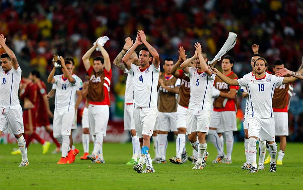 Chile's national team applaud spectators after their victory over Spain during the group B World Cup soccer match between Spain and Chile at the Maracana Stadium in Rio de Janeiro, Brazil.