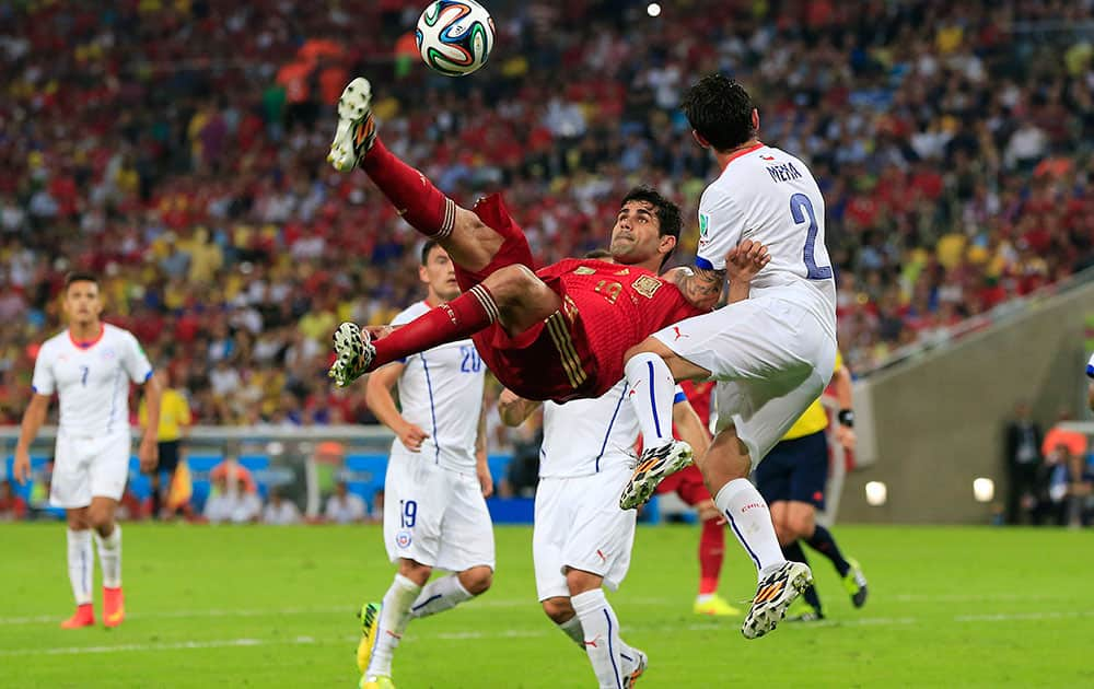 Spain's Diego Costa, left, kicks the ball during the group B World Cup soccer match between Spain and Chile at the Maracana Stadium in Rio de Janeiro, Brazil.