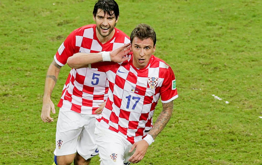 Croatia's Mario Mandzukic (17) celebrates with his teammate Vedran Corluka after scoring his side's third goal during the group A World Cup soccer match between Cameroon and Croatia at the Arena da Amazonia in Manaus, Brazil.