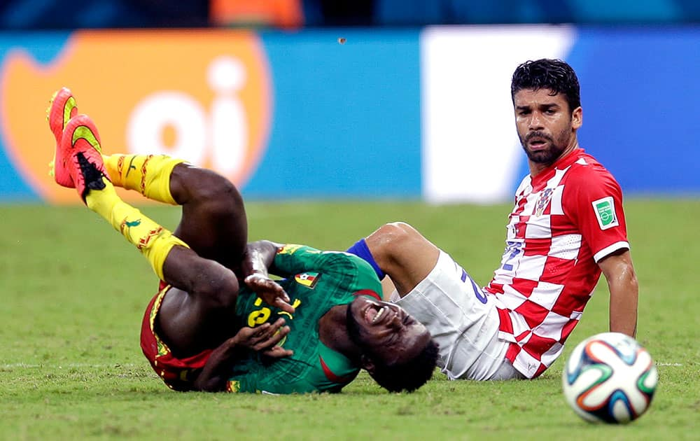 Cameroon's Edgar Salli, left, shouts out after being fouled by Croatia's Eduardo during the group A World Cup soccer match between Cameroon and Croatia at the Arena da Amazonia in Manaus, Brazil.