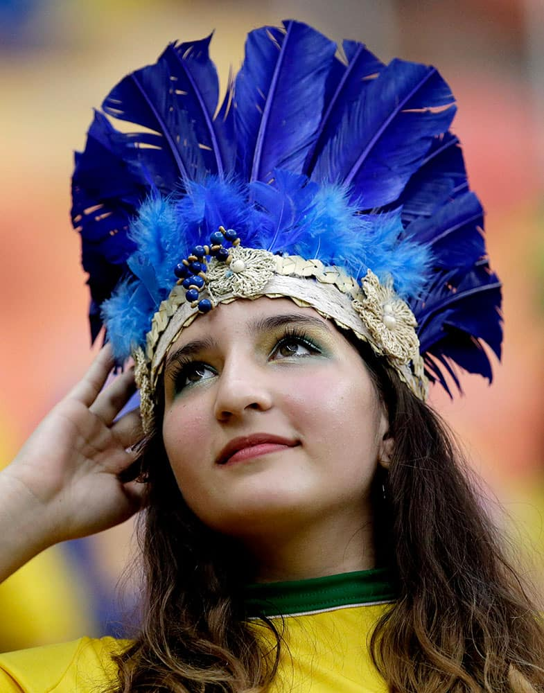 A spectator adjusts her headdress before the start of the group A World Cup soccer match between Cameroon and Croatia at the Arena da Amazonia in Manaus, Brazil.