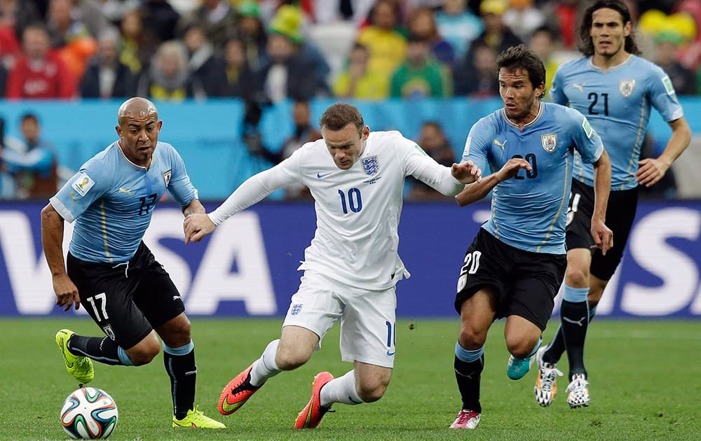 England's Wayne Rooney, second left, takes on the Uruguay defense during the group D World Cup soccer match between Uruguay and England at the Itaquerao Stadium in Sao Paulo, Brazil.