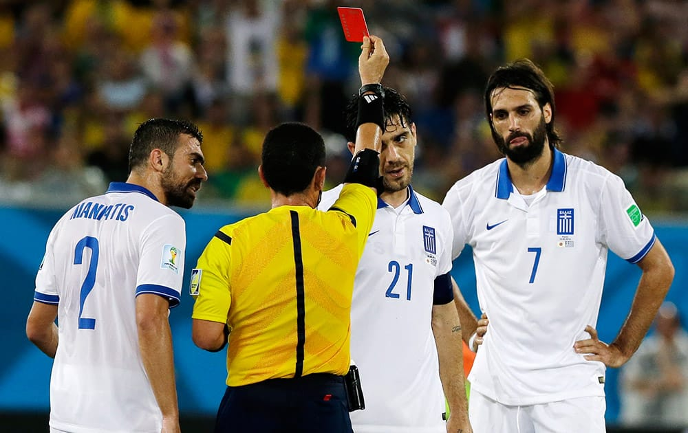 Greece's Kostas Katsouranis (21), Giannis Maniatis (2) and Giorgos Samaras (7) talk with referee Joel Aguilar from El Salvador as he ejects Katsouranis from the match during the group C World Cup soccer match between Japan and Greece at the Arena das Dunas in Natal, Brazil.