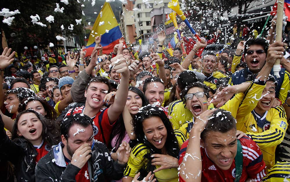 Colombia soccer fans cheer after their team's World Cup victory over Ivory Coast in Bogota, Colombia.
