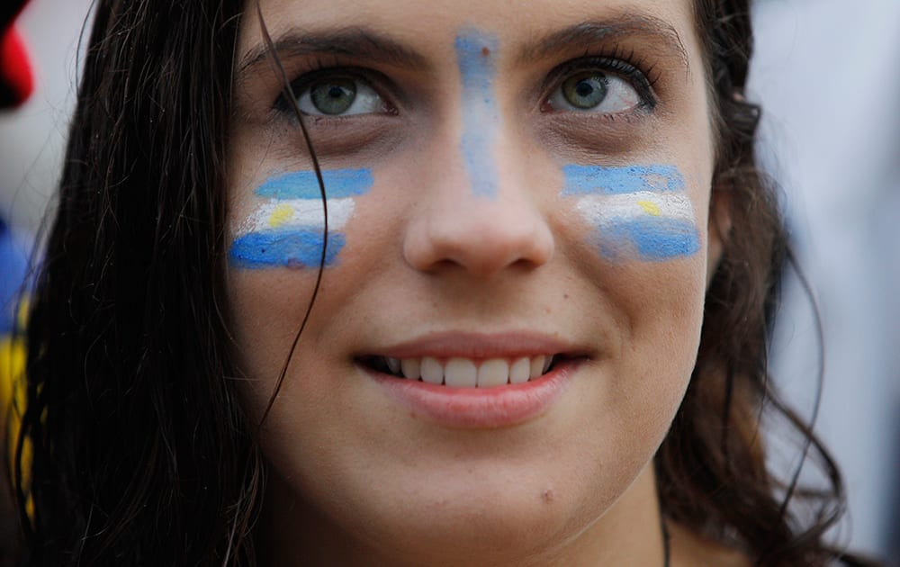 A Soccer fan with her face painted with Uruguay's team colors, watches a live telecast of the group D World Cup match between Uruguay and England, inside the FIFA Fan Fest area on Copacabana beach, in Rio de Janeiro, Brazil.