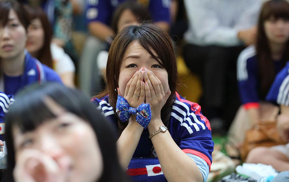 Japanese soccer fans watch a live broadcast of the Group C World Cup soccer match between Japan and Greece at a public viewing venue set up at Marunouchi business district in Tokyo.