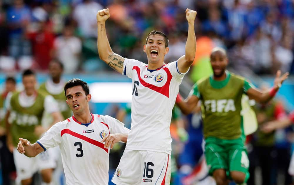 Costa Rica's Cristian Gamboa (16) and Giancarlo Gonzalez (3) celebrate with Oscar Duarte after the team's 1-0 victory over Italy during the group D World Cup soccer match between Italy and Costa Rica at the Arena Pernambuco in Recife, Brazil.