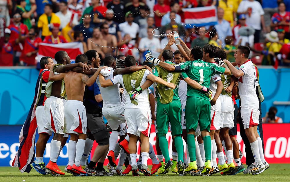 Costa Rican players celebrate after the group D World Cup soccer match between Italy and Costa Rica at the Arena Pernambuco in Recife, Brazil.