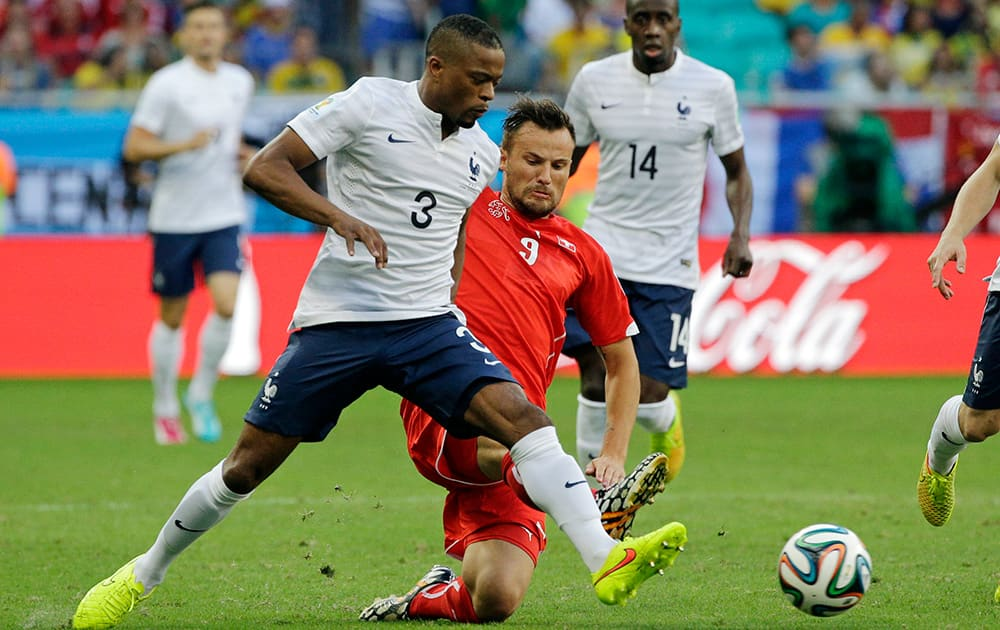 Switzerland's Haris Seferovic, right, challenges France's Patrice Evra during the group E World Cup soccer match between Switzerland and France at the Arena Fonte Nova in Salvador, Brazil.