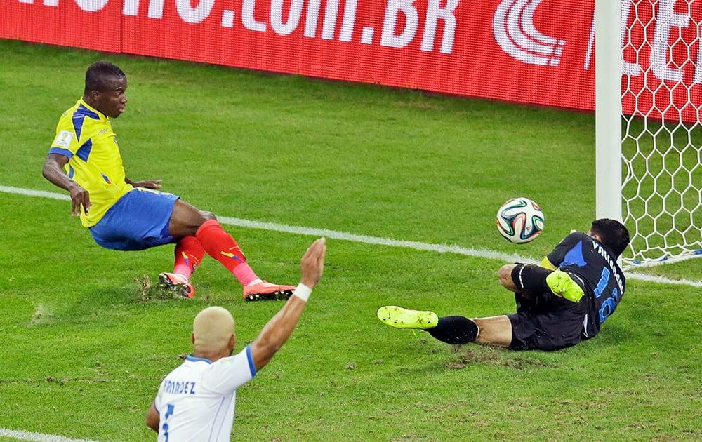 Ecuador's Enner Valencia, left, scores his side's first goal past Honduras' goalkeeper Noel Valladares during the group E World Cup soccer match between Honduras and Ecuador at the Arena da Baixada in Curitiba, Brazil.