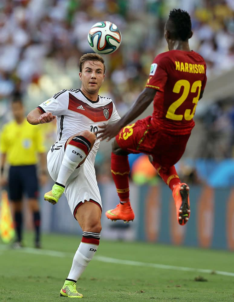 Ghana's Harrison Afful, right, comes in to block the ball from Germany's Mario Goetze during the group G World Cup soccer match between Germany and Ghana at the Arena Castelao in Fortaleza, Brazil.