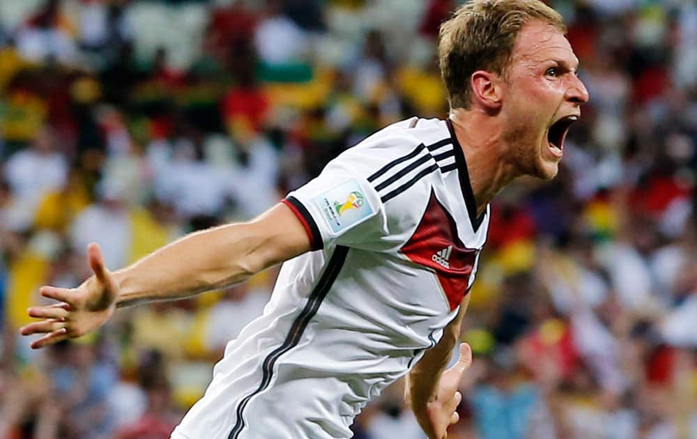 Germany's Benedikt Hoewedes celebrates after his teammate Miroslav Klose scored a goal during the group G World Cup soccer match between Germany and Ghana at the Arena Castelao in Fortaleza, Brazil.
