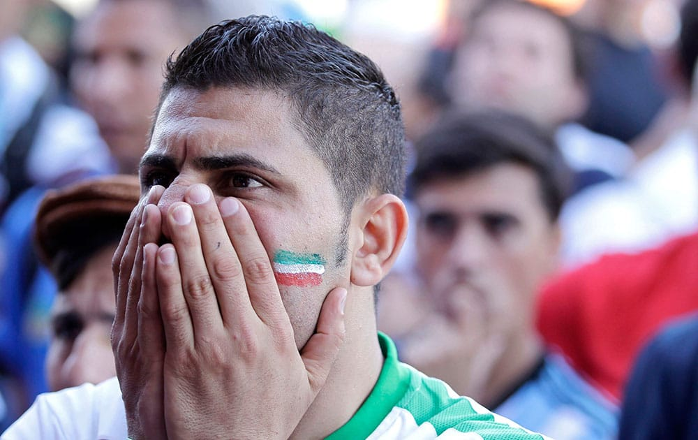 An Iran soccer fan watches his team loose 1-0 to Argentina on TV at a bar near Minerao Stadium, where the game takes place in Belo Horizonte, Brazil.