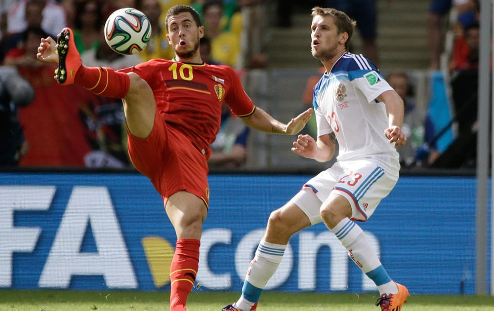 Belgium's Eden Hazard, left, is challenged by Russia's Dmitry Kombarov during the group H World Cup soccer match between Belgium and Russia at the Maracana Stadium in Rio de Janeiro, Brazil.