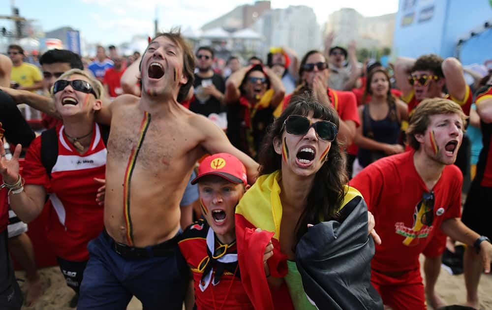 Soccer fans react as they watch a live broadcast of the group H World Cup match between Belgium and Russia inside the FIFA Fan Fest area on Copacabana beach, in Rio de Janeiro, Brazil.
