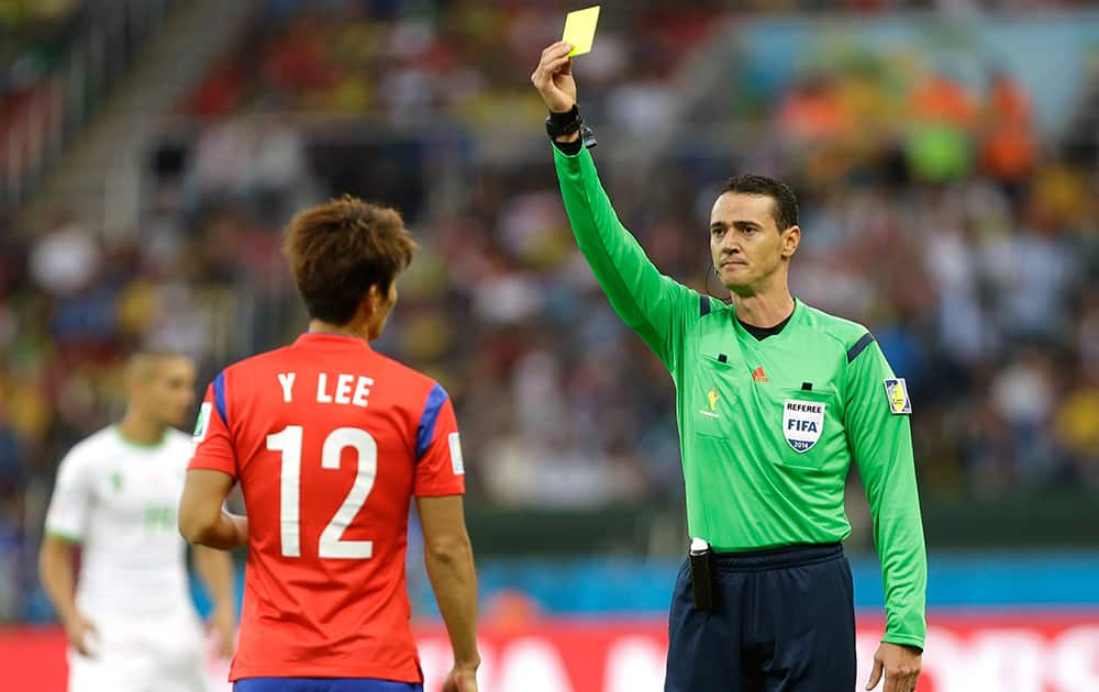 Referee Wilmar Roldan from Colombia shows a yellow card to South Korea's Lee Yong during the group H World Cup soccer match between South Korea and Algeria at the Estadio Beira-Rio in Porto Alegre, Brazil.
