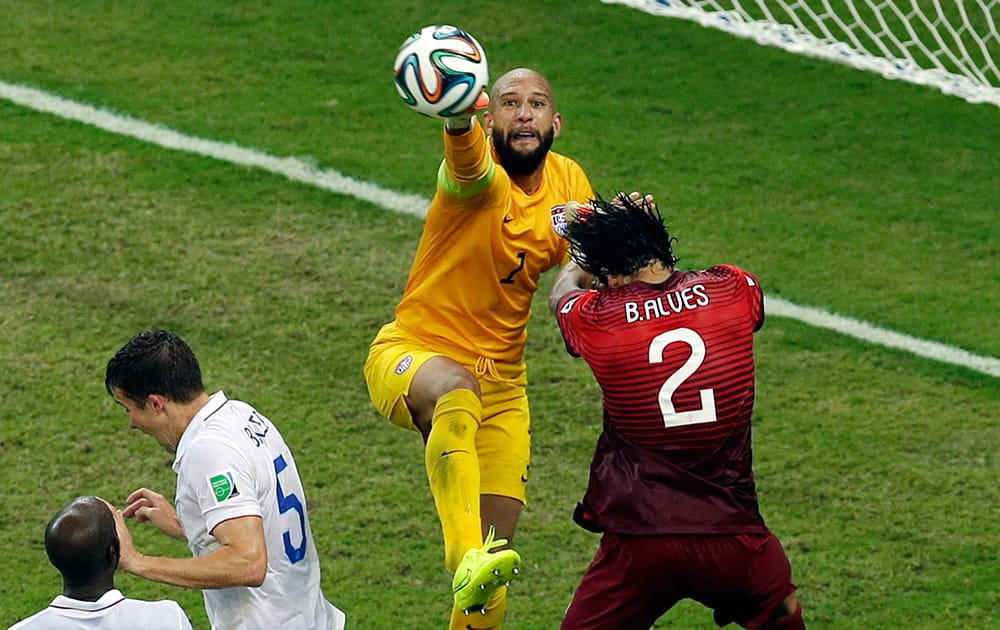 United States' goalkeeper Tim Howard reaches a ball ahead of Portugal's Bruno Alves during the group G World Cup soccer match between the USA and Portugal at the Arena da Amazonia in Manaus, Brazil.