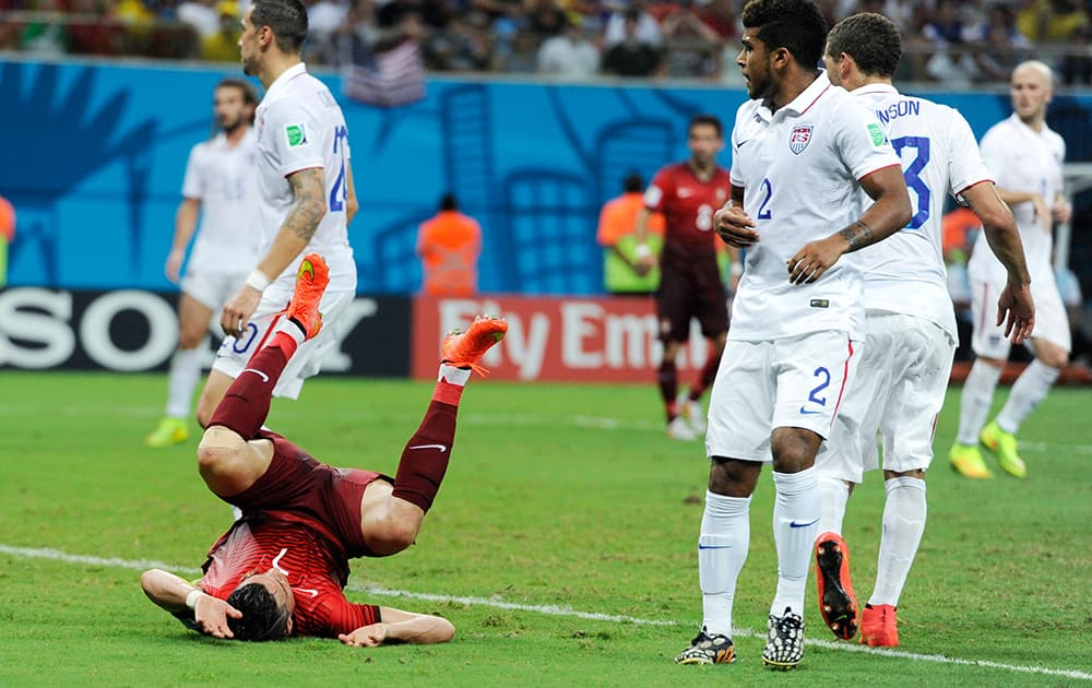 Portugal's Cristiano Ronald, lower left, takes a tumble during the group G World Cup soccer match between the USA and Portugal at the Arena da Amazonia in Manaus, Brazil.
