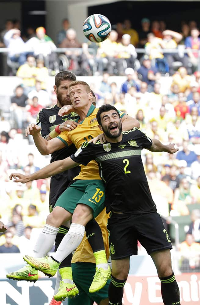 Spain's Sergio Ramos, left, Australia's Oliver Bozanic and Spain's Raul Albiol go for a header during the group B World Cup soccer match between Australia and Spain at the Arena da Baixada in Curitiba, Brazil.