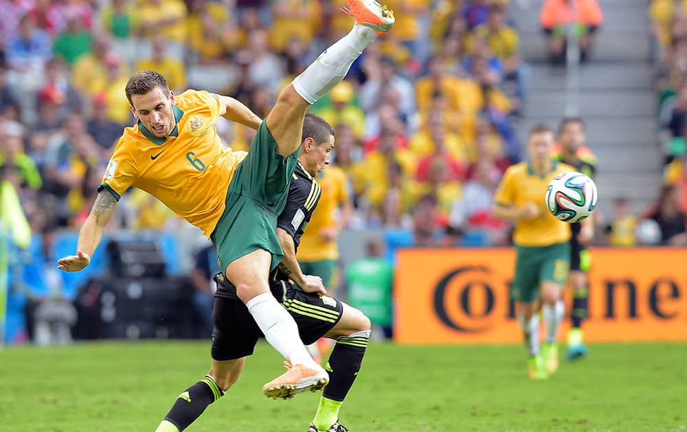 Australia's Matthew Spiranovic and Spain's Fernando Torres fight for the ball during the group B World Cup soccer match between Australia and Spain at the Arena da Baixada in Curitiba, Brazil.